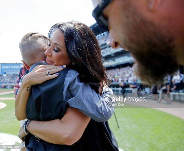 Jamie Buehrle hugs her son Braden after he sung the national anthem as his dad and former Chicago White Sox pitcher Mark Buehrle watches following...