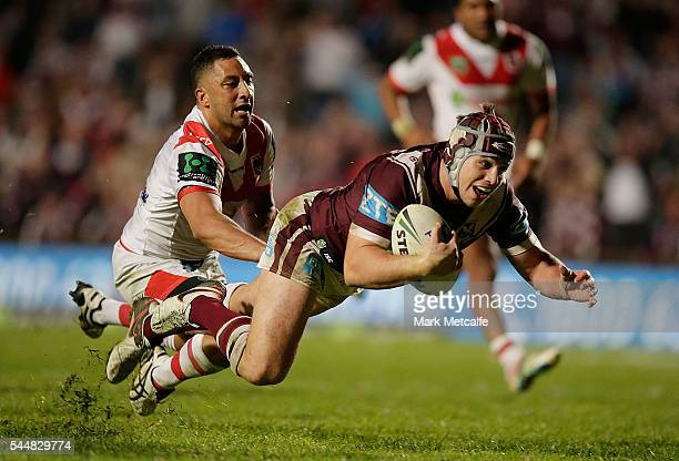 Jamie Buhrer of the Sea Eagles evades the tackle of Benji Marshall of the Dragons to score a try during the round 17 NRL match between the Manly Sea...