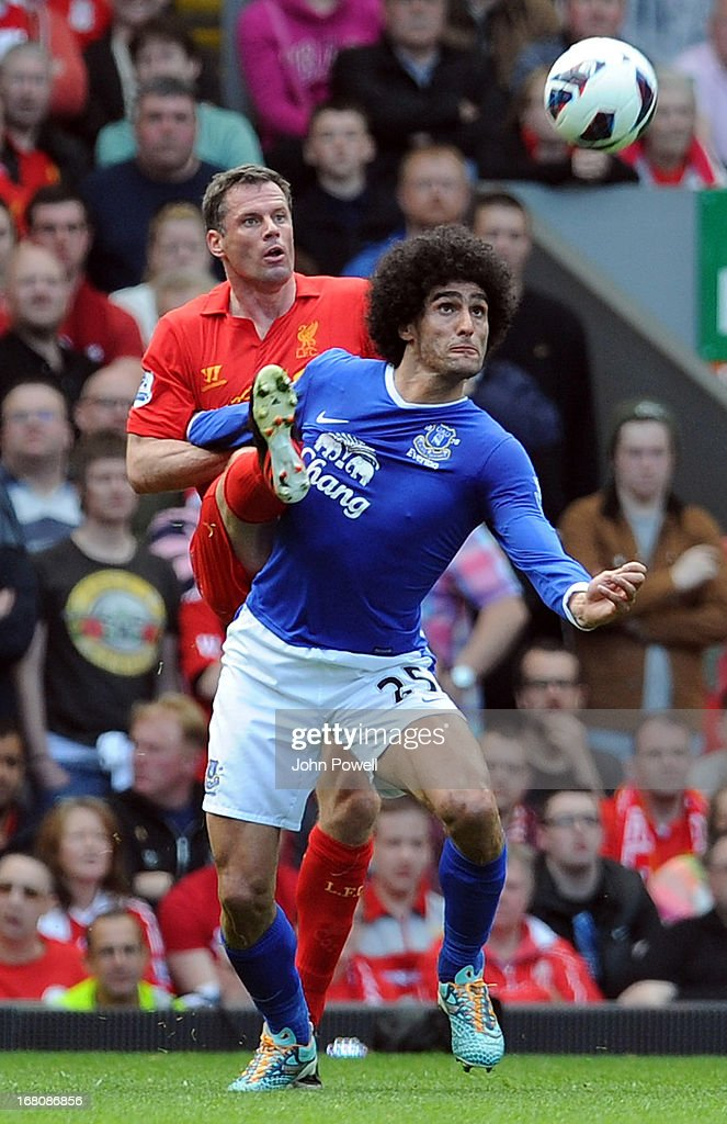 Jamie Carragher of Liverpool and Marouane Fellaini of Everton compete during the Barclays Premier League match between Liverpool and Everton at Anfield on May 5, 2013 in Liverpool, England.