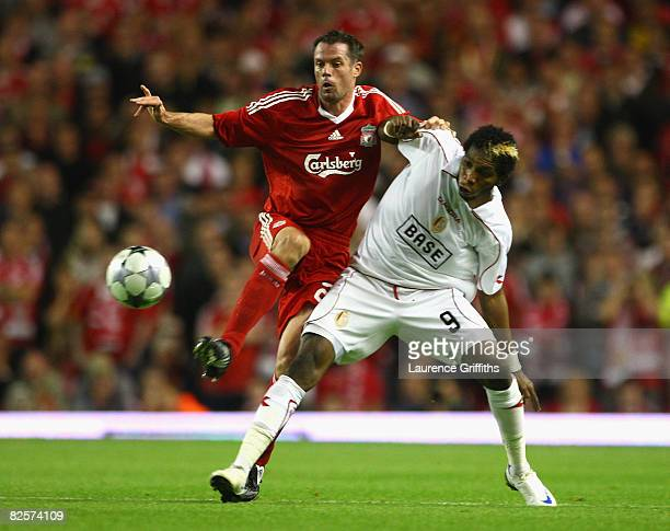 Jamie Carragher of Liverpool battles with Dieumerci Mbokani of Standard Liege during the UEFA Champions League Qualifier Third Round second Leg Match...