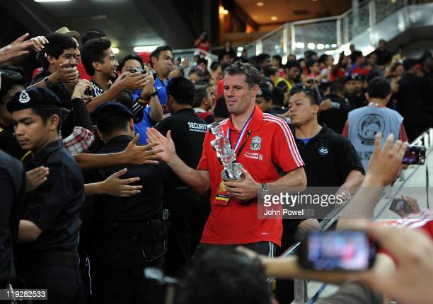 Jamie Carragher of Liverpool lifts a trophy after the preseason friendly match between Malaysia and Liverpool at Bukit Jalil National Stadium on July...