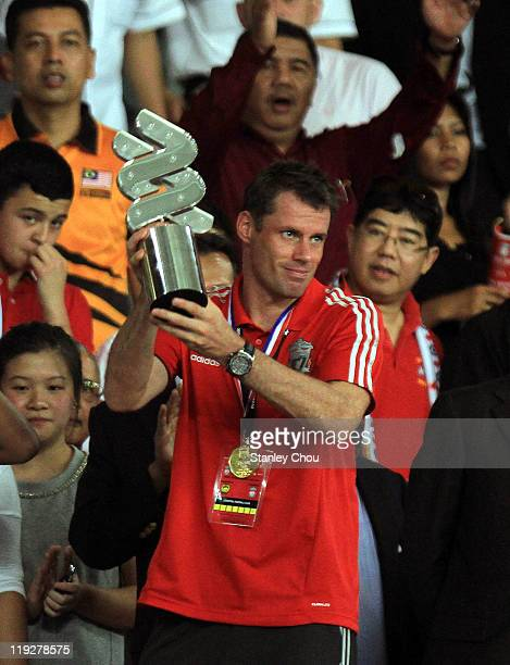 Jamie Carragher of Liverpool lifts the Chartered Bank trophy after his team defeated Malaysia 63 during the preseason friendly match between Malaysia...