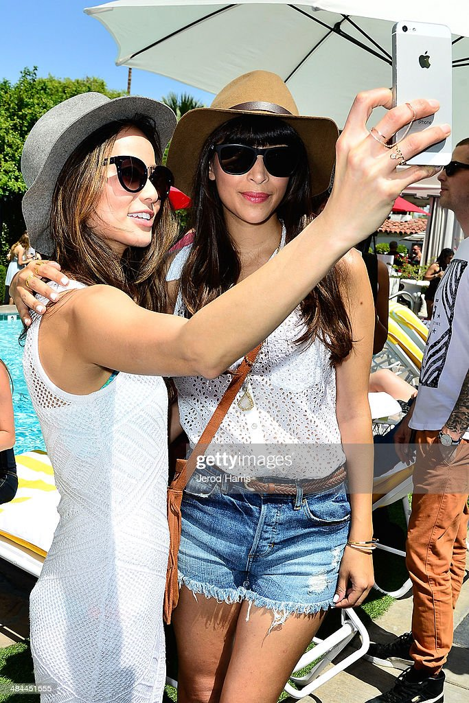 Jamie Chung and Hannah Simone pose for a selfie at the GUESS Hotel at the Viceroy Palm Springs on April 12, 2014 in Palm Springs, California.