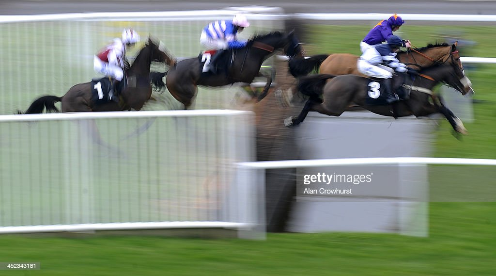 Jamie Codd riding Top Dancer (purple/orange) clear the water jump on their way to winning The Burges Salmon Amateur Riders' Handicap Steeple Chase at Newbury racecourse on November 28, 2013 in Newbury, England.