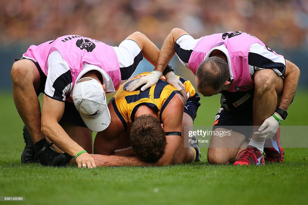 Jamie Cripps of the Eagles is checked by the clubs physio and doctor during the round 10 AFL match between the West Coast Eagles and the Gold Coast Suns at Domain Stadium on May 29, 2016 in Perth, Australia.