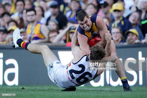Jamie Cripps of the Eagles is tackled by Richard Douglas of the Crows during the round 23 AFL match between the West Coast Eagles and the Adelaide...