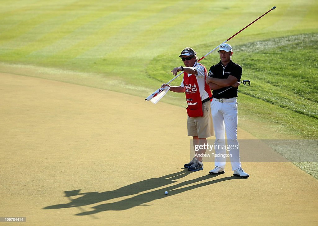 Jamie Donaldson of Wales and his caddie Mick Donaghy line up a putt on the 18th hole during The Abu Dhabi HSBC Golf Championship at Abu Dhabi Golf Club on January 20, 2013 in Abu Dhabi, United Arab Emirates.