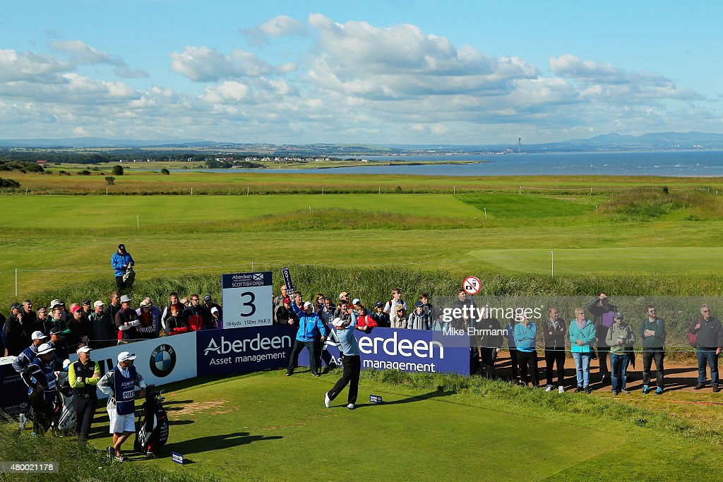 Jamie Donaldson of Wales hits his tee shot on the third hole as a gallery of patrons look on during the first round of the Aberdeen Asset Management...