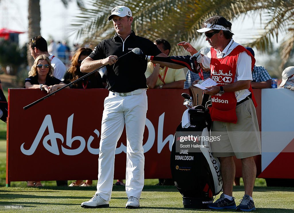 Jamie Donaldson of Wales pulls a club on the 14th tee alongside his caddie Mick Donaghy during the final round of the Abu Dhabi HSBC Golf Championship at Abu Dhabi Golf Club on January 20, 2013 in Abu Dhabi, United Arab Emirates.