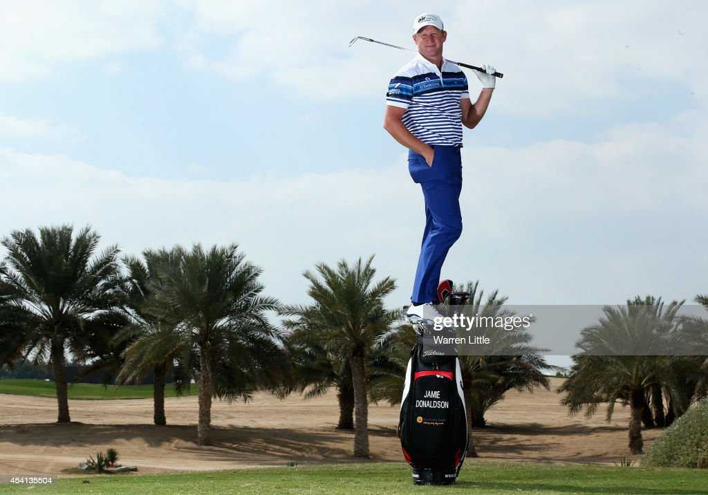Jamie Donaldson of Wales strikes a pose on top of his bag ahead of the Abu Dhabi HSBC Golf Championship at Abu Dhabi Golf Club on January 14 2014 in...