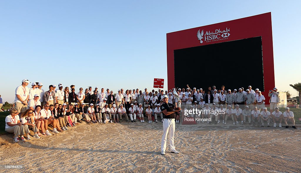 Jamie Donaldson of Wales with the winners trophy and the volunteers after the final round of the Abu Dhabi HSBC Golf Championship at the Abu Dhabi Golf Club on January 20, 2013 in Abu Dhabi, United Arab Emirates.