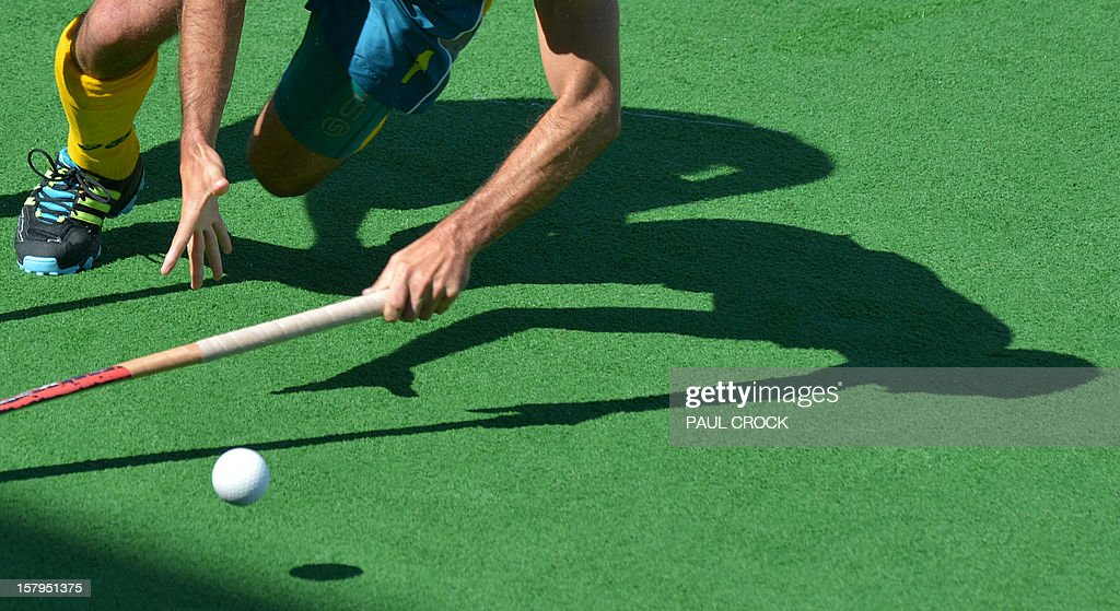 Jamie Dwyer of Australia (L) chases down the ball against India during the second semifinal at the men's Hockey Champions Trophy tournament in Melbourne on December 8, 2012. IMAGE STRICTLY RESTRICTED TO EDITORIAL USE - STRICTLY NO COMMERCIAL USE AFP PHOTO / Paul CROCK