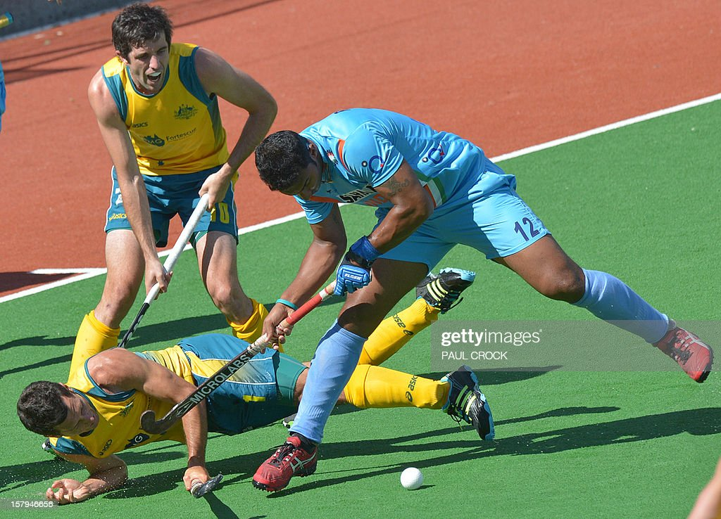 Jamie Dwyer of Australia (L) is falls next to Raghunath Vr of India (R) in the second semi final at the men's Hockey Champions Trophy in Melbourne on December 8, 2012. IMAGE STRICTLY RESTRICTED TO EDITORIAL USE - STRICTLY NO COMMERCIAL USE AFP PHOTO / Paul CROCK