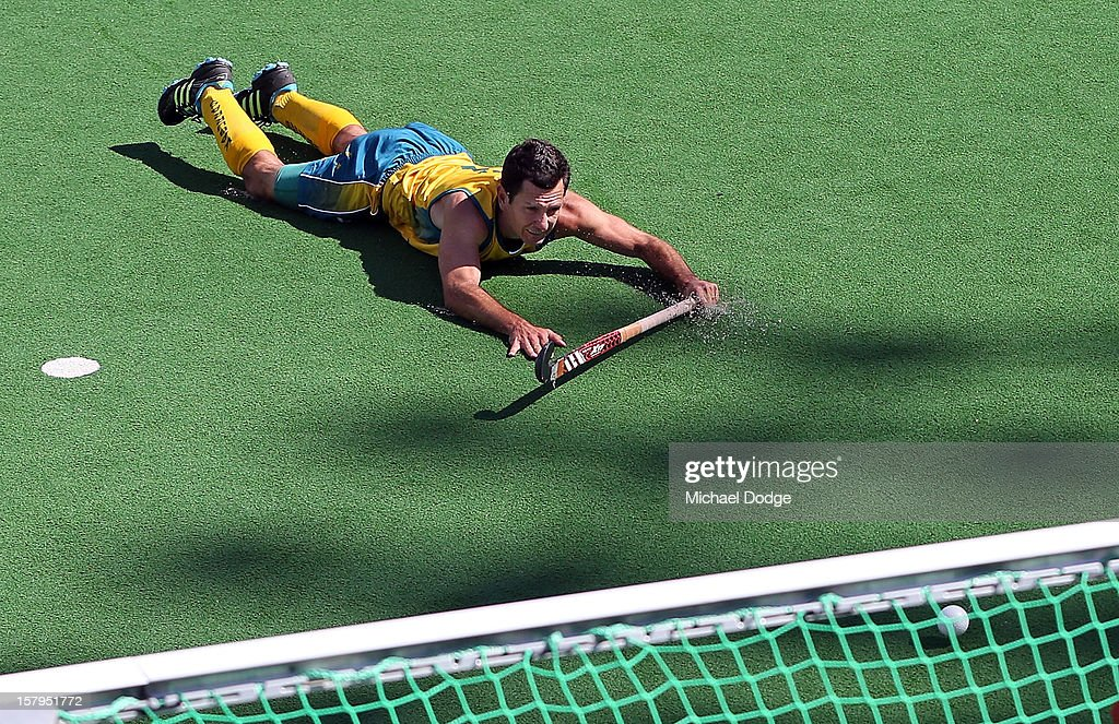 Jamie Dywer of Australia dives and hits the ball for a goal attempt in the match between Australia and India during day five of the 2012 Champions Trophy at the State Netball and Hockey Centre on December 8, 2012 in Melbourne, Australia.