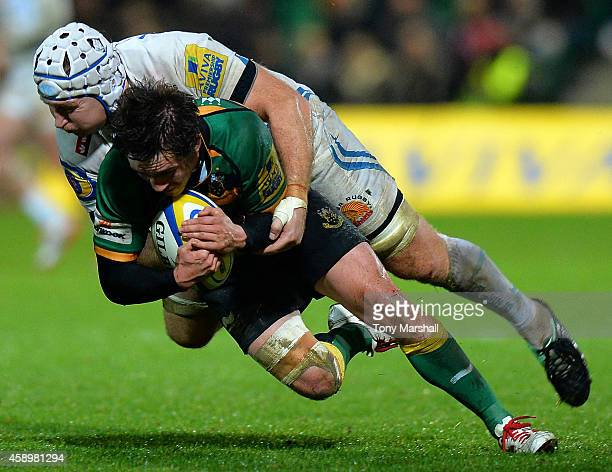 Jamie Elliott of Northampton Saints is tackled by Thomas Waldrom of Exeter Chiefs during the Aviva Premiership match between Northampton Saints and...