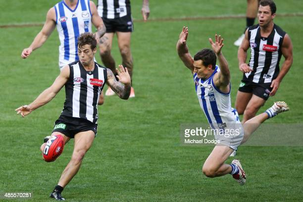Jamie Elliott of the Magpies kicks the ball away from Scott Thompson of the Kangaroos during the round five AFL match between the Collingwood Magpies...