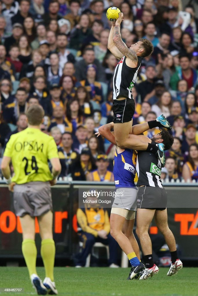Jamie Elliott of the Magpies leaps for a high mark attempt but drops the ball during the round 10 AFL match between the Collingwood Magpies and West Coast Eagles at Melbourne Cricket Ground on May 24, 2014 in Melbourne, Australia.