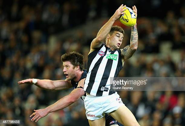 Jamie Elliott of the Magpies marks over the top of Sam Rowe of the Blues during the round seven AFL match between the Carlton Blues and the...