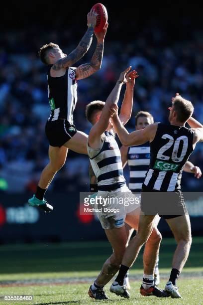 Jamie Elliott of the Magpies marks the ball against Zac Smith of the Cats during the round 22 AFL match between the Collingwood Magpies and the...