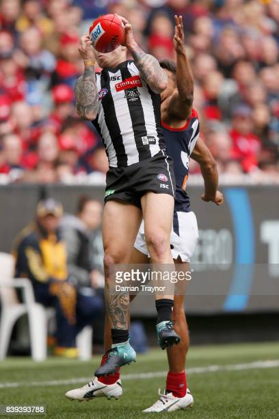 Jamie Elliott of the Magpies marks the ball in front of Neville Jetta of the Demons during the round 23 AFL match between the Collingwood Magpies and...