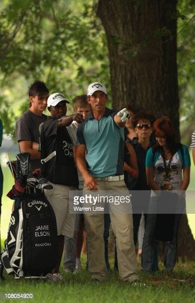 Jamie Elson of England consults his caddie before chipping out of the trees on the eighth hole during the third round of the Joburg Open at Royal...