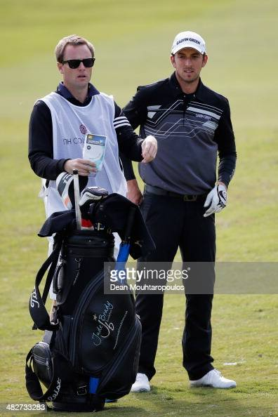 Jamie Elson of England looks on with his caddie before he hits his second shot on the 9th hole during day two of the NH Collection Open held at La...