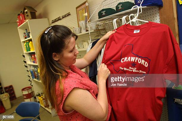 Jamie Faichtinger arranges President George W Bush souvenir teeshirts on store shelves April 13 2001 in Crawford Texas Crawford the hometown of US...