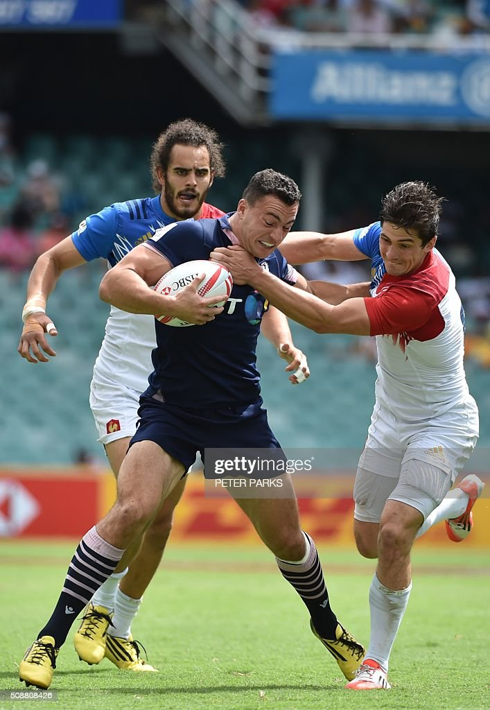 Jamie Farndale of Scotland (C) is tackled by Steeve Barry of France (R) as his teammate Jonathan Laugel (L) looks on, during their Bowl quarter-final game in the Sydney Sevens rugby union tournament in Sydney on February 7, 2016. AFP PHOTO / Peter PARKS PARKS
