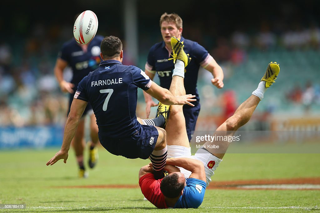 Jamie Farndale of Scotland passes as he is tackled by Damien Cler of France during the 2016 Sydney Sevens match between at Allianz Stadium on February 7, 2016 in Sydney, Australia.