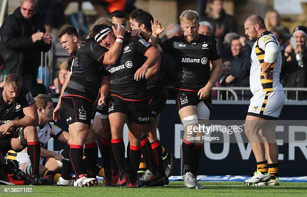 Jamie George of Saracens is congratulated by team mate Petrus du Plessis after scoring their third try during the Aviva Premiership match between...