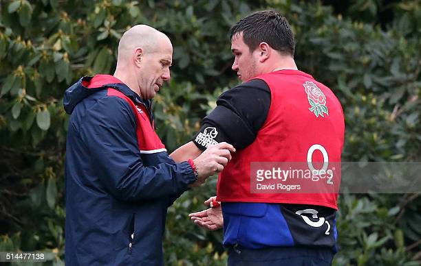 Jamie George receives attention from physio Phil Pask to his injiured left arm during the England training session held at Pennyhill Park on March 8...