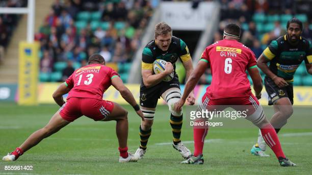 Jamie Gibson of Northampton takes on Joe Marchant and Ben Glynn during the Aviva Premiership match between Northampton Saints and Harlequins at...