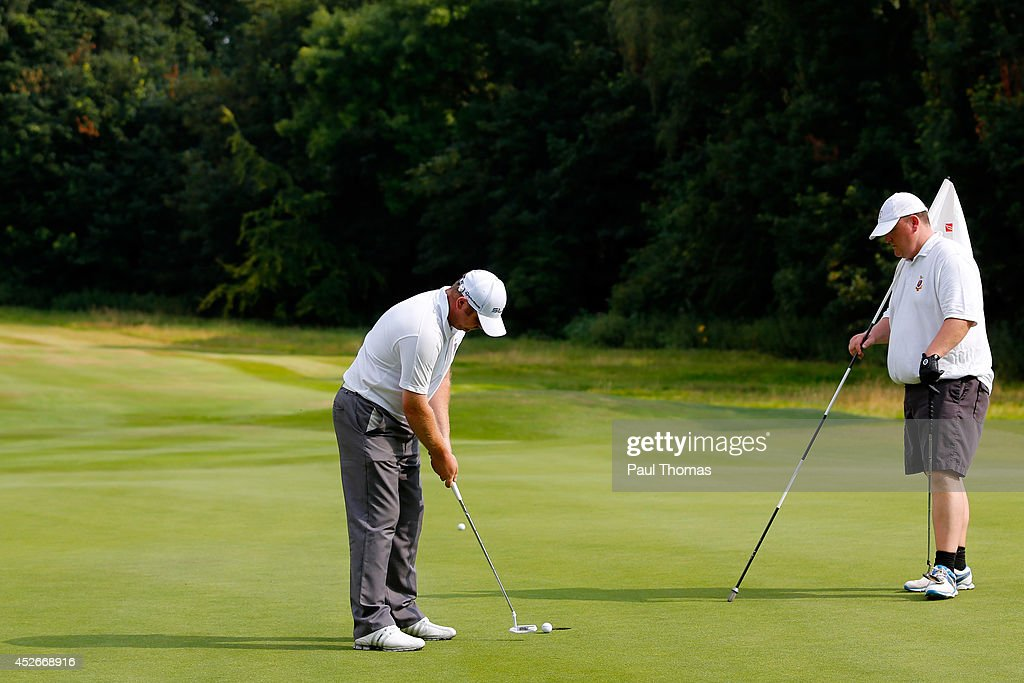 Jamie Goodhall of Glossop & District Golf Club putts while being watched by team mate Jason Eyre during The Lombard Trophy North West Regional Qualifier at Dunham Forest Golf Club on July 25, 2014 in Altrincham, England.