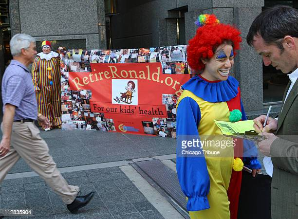 Jamie Gordon a Corporate Accountability International staff member dresses as a clown as she gets signatures outside Leo Burnett's office in Chicago...