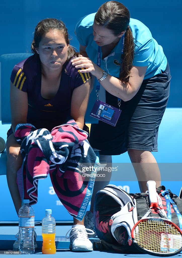 Jamie Hampton of the US (L) receives treatment during her women's singles match against Belarus's Victoria Azarenka on the sixth day of the Australian Open tennis tournament in Melbourne on January 19, 2013.