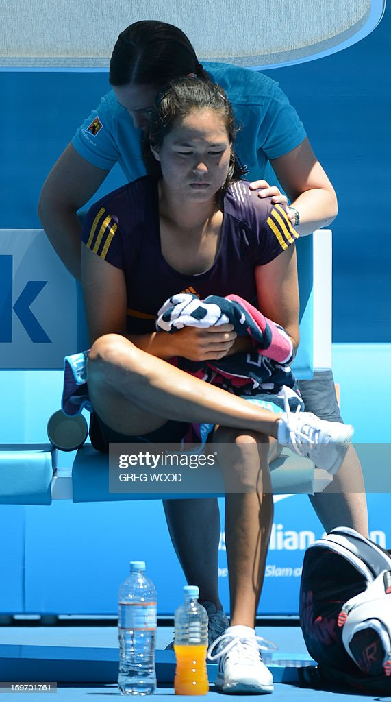Jamie Hampton of the US receives treatment during her women's singles match against Belarus's Victoria Azarenka on the sixth day of the Australian Open tennis tournament in Melbourne on January 19, 2013.