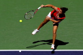 Jamie Hampton serves to Jelena Jankovic of Serbia during the BNP Paribas Open at the Indian Wells Tennis Garden on March 9 2012 in Indian Wells...