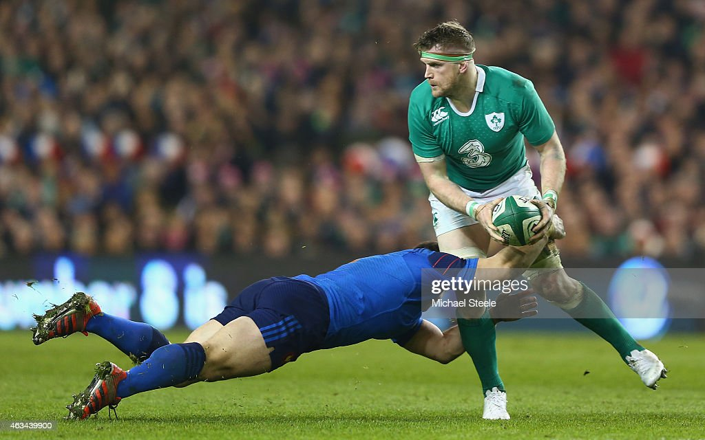 Jamie Heaslip of Ireland looks for support as Guilhem Guirado of France holds on during the RBS Six Nations match between Ireland and France at the...