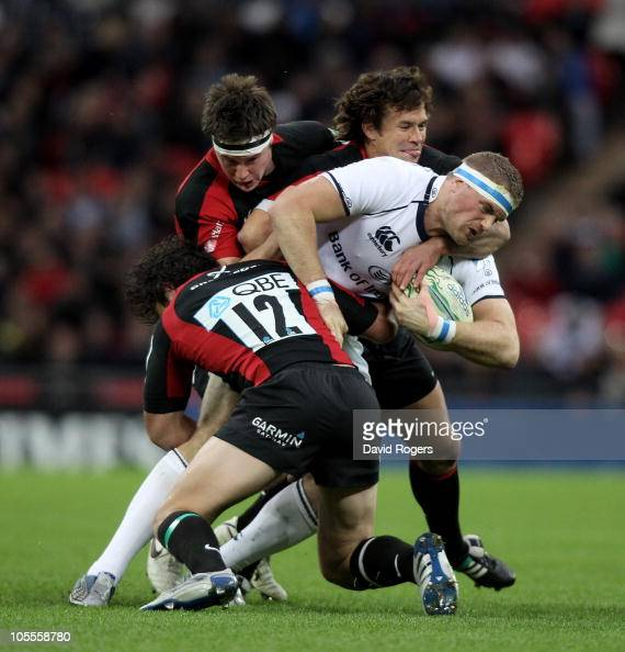 Jamie Heaslip of Leinster is tackled by Brad Barritt Andy Saull and Derick Hougaard during the Heineken Cup match between Saracens and Leinster at...