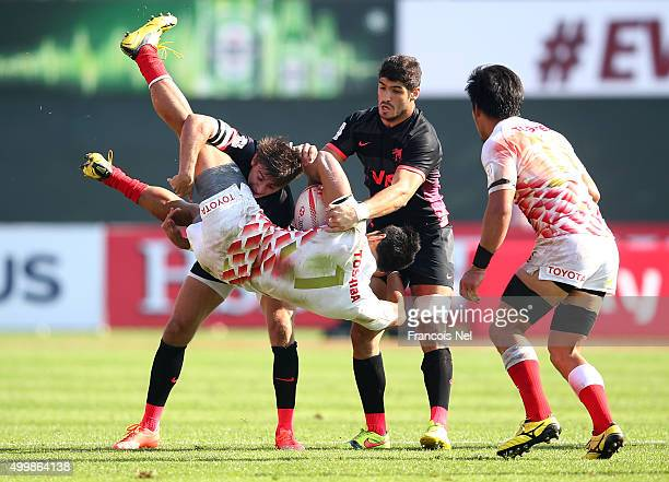 Jamie Henry of Japan is tackled by Sebastian Cancelliere of Argentina during the Emirates Dubai Rugby Sevens HSBC Sevens World Series on December 4...