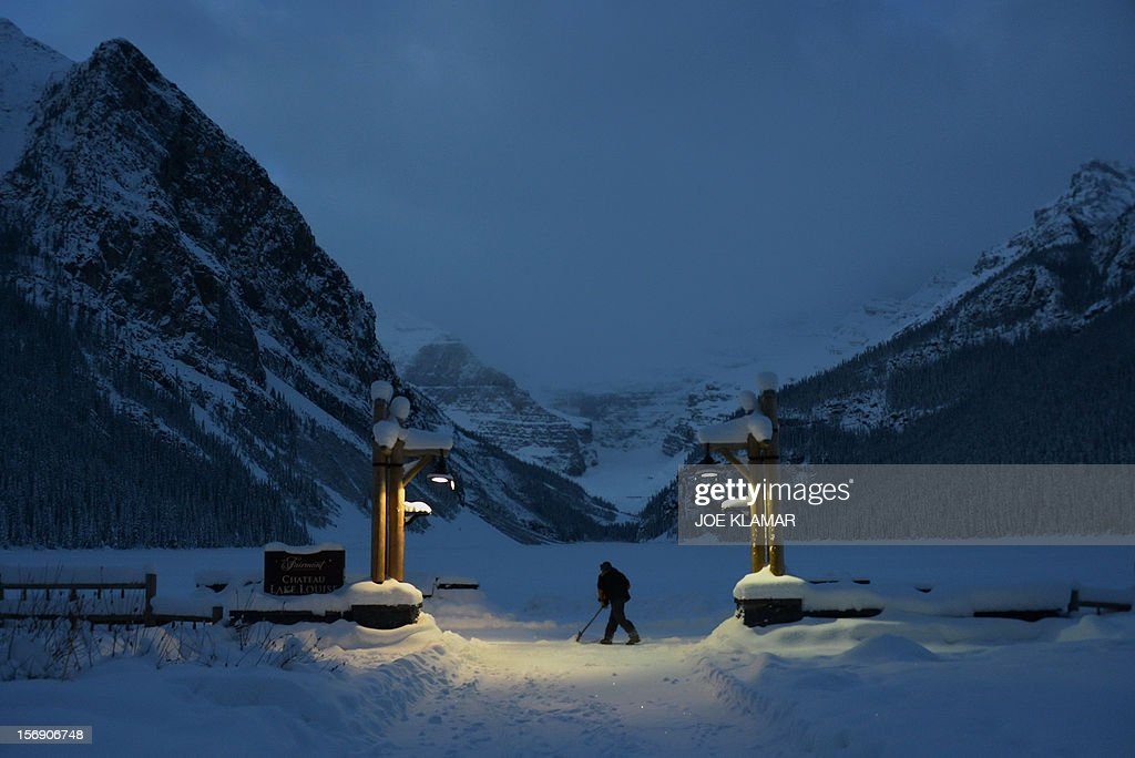 Jamie, hotel worker, of Fairmont Chateau Hotel shovels a snow between the hotel and a gateway to the Lake Louise early morning in Lake Louise, Alberta on November 24, 2012. Lake Louise, famous Canadian winter and summer resort located in Banff National Park hosts men's and women's World Cup in Alpine skiing.