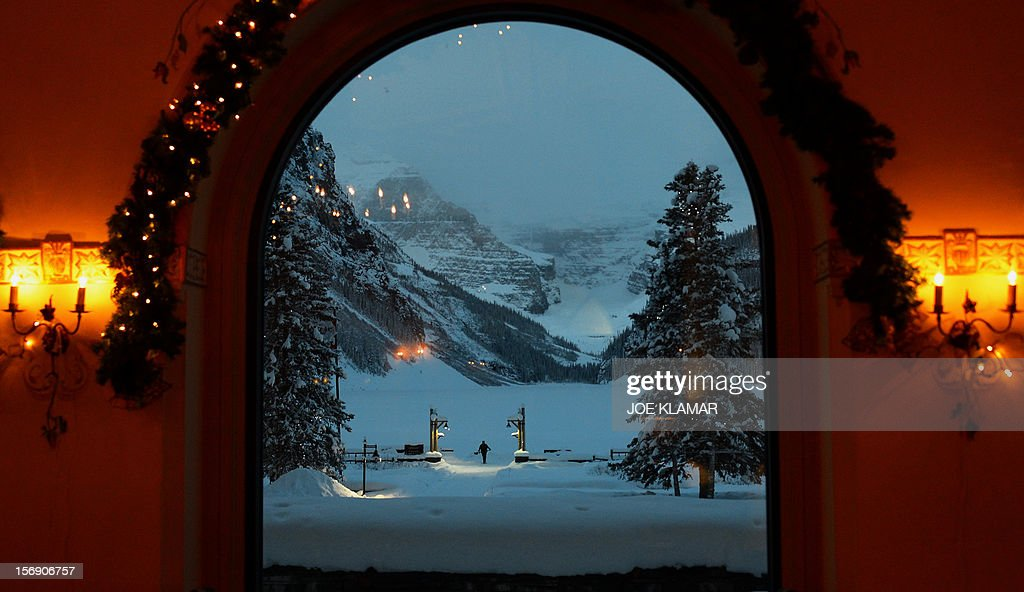 Jamie, hotel worker, of Fairmont Chateau Hotel shovels a snow between the hotel and a gateway to the Lake Louise early morning in Lake Louise, Alberta on November 24, 2012. Lake Louise, famous Canadian winter and summer resort located in Banff National Park hosts men's and women's World Cup in Alpine skiing. AFP PHOTO / JOE KLAMAR