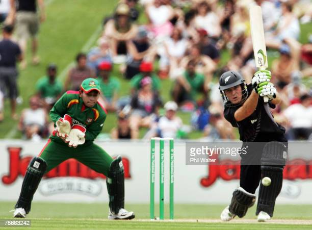 Jamie How of New Zealand plays a shot in front of Mushifiqur Rahim of Bangladesh during the second one day international match between New Zealand...