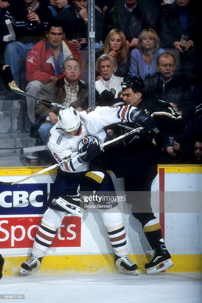 Jamie Langenbrunner of the Dallas Stars is checked into the boards by Bill Guerin of the Edmonton Oilers during Game 3 of the 2000 Conference...