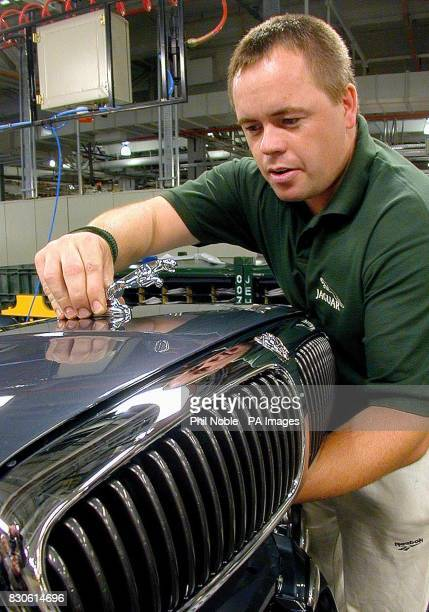 Jamie Lovett fixes the famous leaping Jaguar on top of the bonnet of the new Jaguar XType at a photocall to mark the official opening of the Halewood...