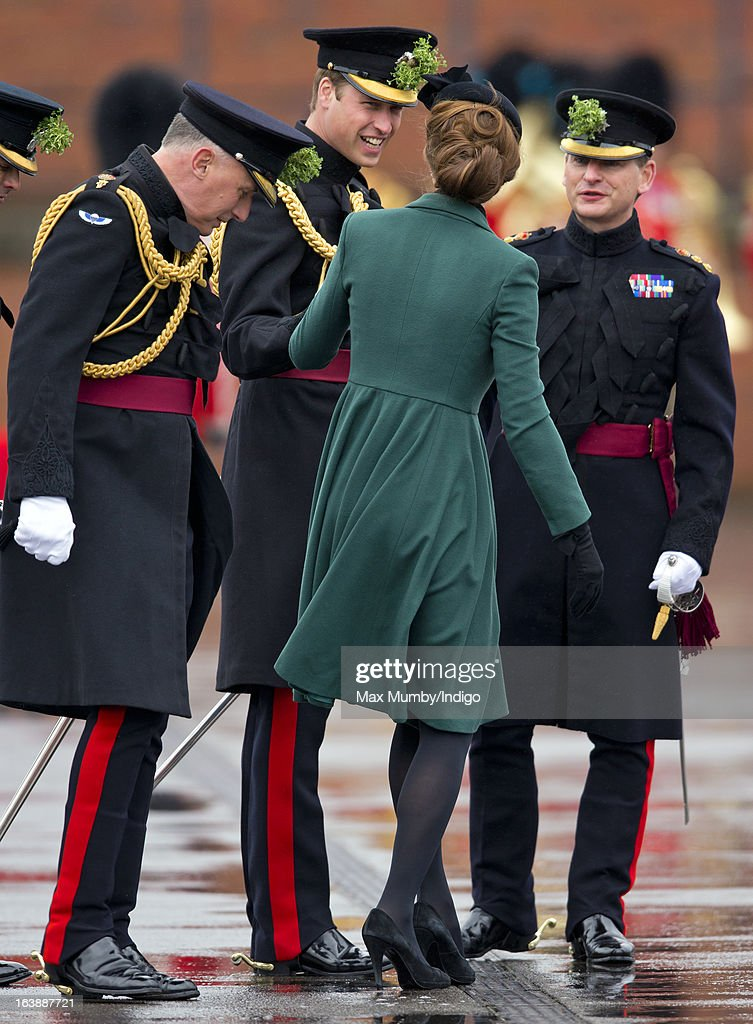 Jamie Lowther-Pinkerton looks on as Prince William, Duke of Cambridge (in his role as Colonel of the Regiment) helps his wife Catherine, Duchess of Cambridge as she gets the heel of her shoe stuck in a grate as they attend the St Patrick's Day Parade at Mons Barracks on March 17, 2013 in Aldershot, England.