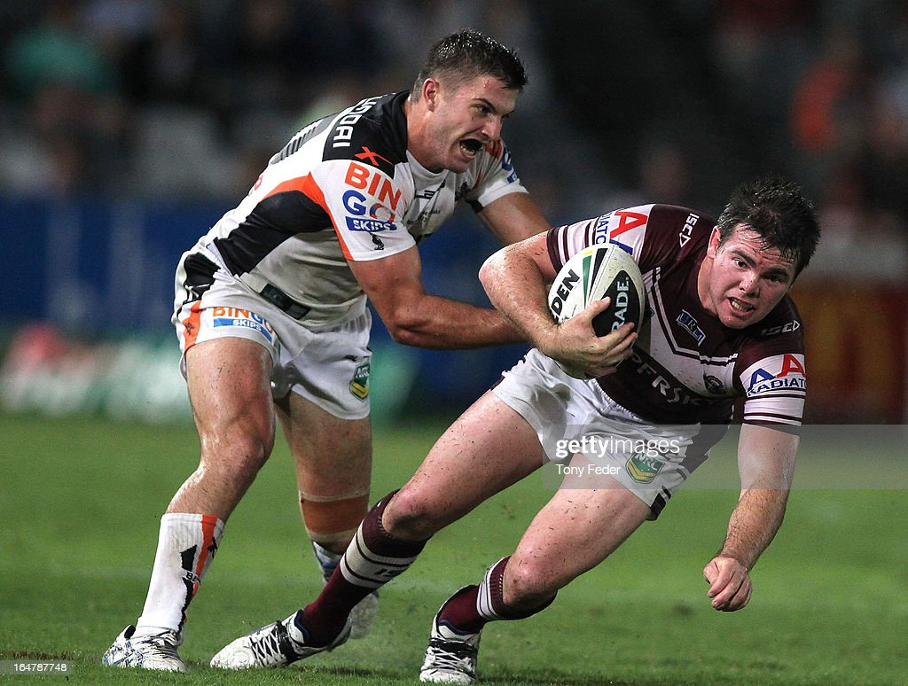 Jamie Lyon of the Sea Eagles is tackled by James Tedesco of the Wests Tigers during the round four NRL match between the Manly Sea Eagles and the Wests Tigers at Bluetongue Stadium on March 28, 2013 in Gosford, Australia.