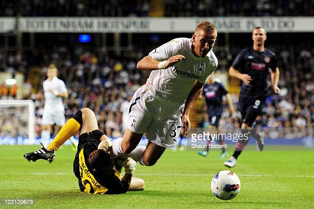 Jamie Macdonald of Hearts fouls Harry Kane of Tottenham Hotspur during the UEFA Europa League playoff match between Tottenham Hotspur FC and Heart of...