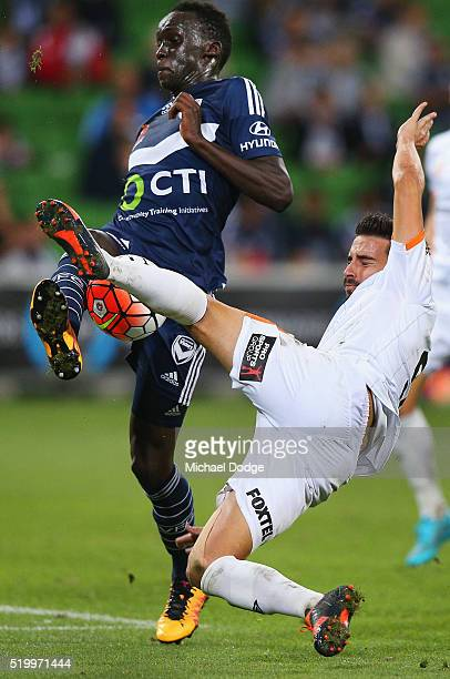 Jamie Maclaren of Brisbane Roar kicks the ball against Thomas Deng of the Victory during the round 27 ALeague match between the Melbourne Victory and...