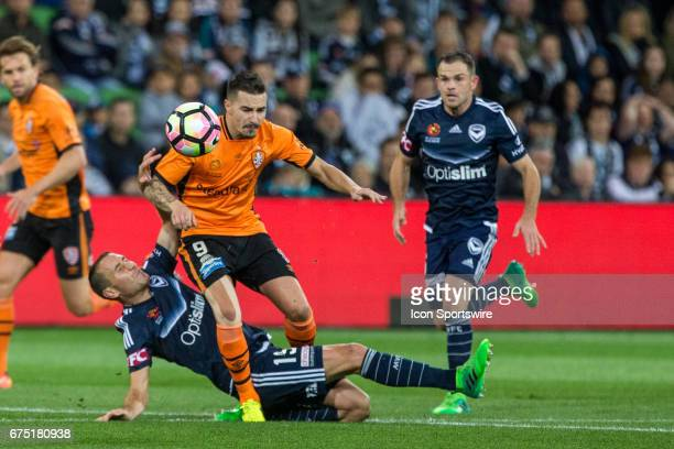Jamie Maclaren of the Brisbane Roar jumps over a downed Alan Baro of Melbourne Victory chasing after the ball during the Semi Final Match of the...